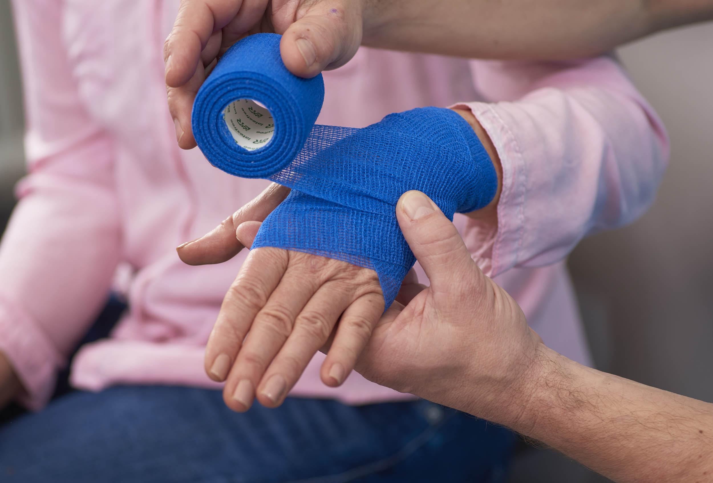 Arzt legt Verband um die Hand nach einem handchirurgischen Eingriff